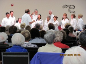 9 singers and Director Dr. Tony Godlefski of The Starlite Chorale all in white shirts and black pants as viewed from the back of the performance hall
